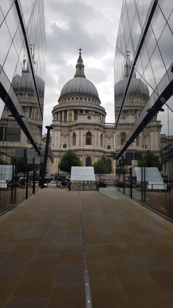 Photograph of St Paul's Cathedral taken between two large glass buildings so that the cathedral reflects against them. The Cathedral is limestone with arches, pillars and a large domed roof