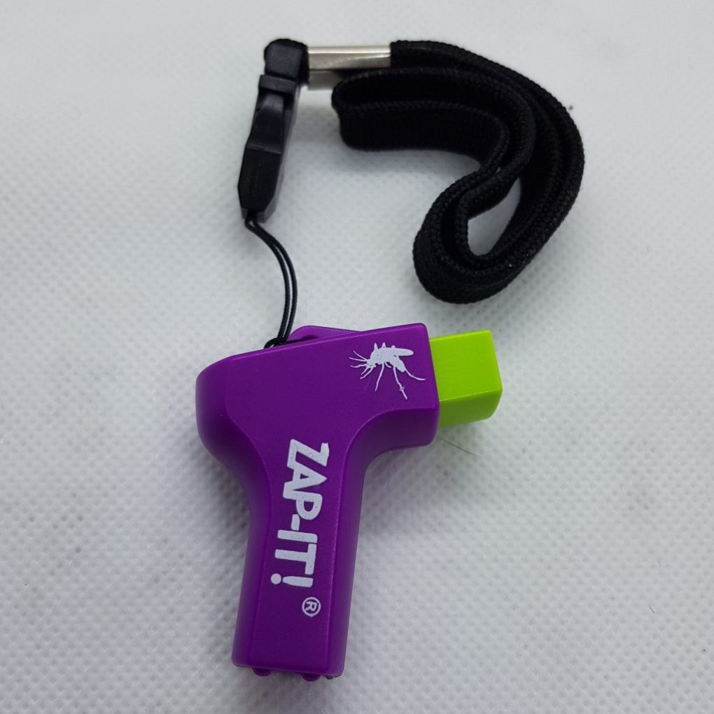 A purple gun shaped device with a green button, white writing saying Zap-it! and a black string loop for attaching the device to bags ect.