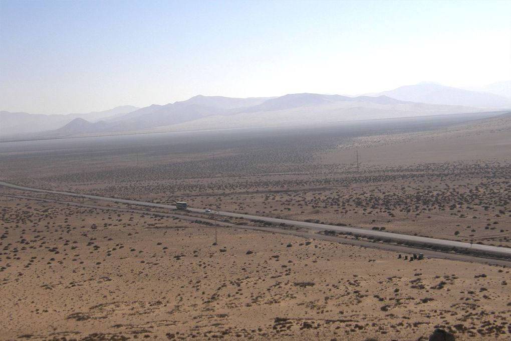 A stretch of road surrounded by dessert and mountains