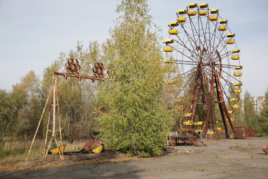 An abandoned theme park with broken swings and a Ferris Wheel