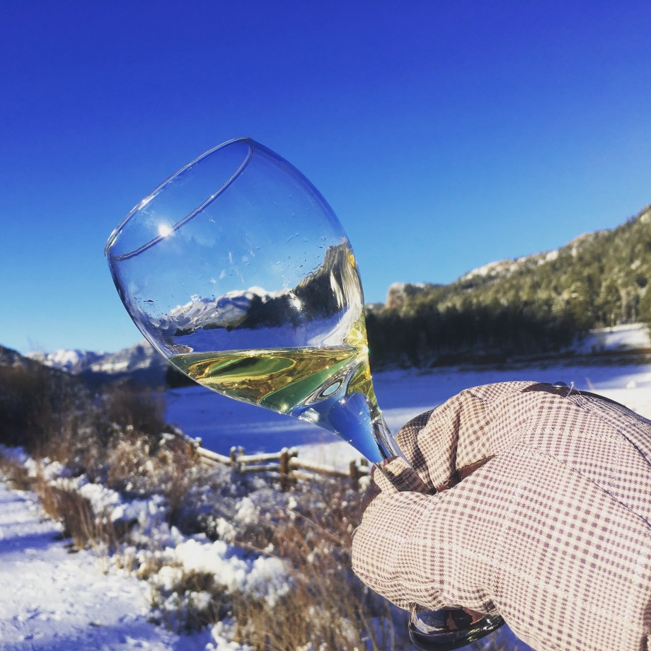 A glass of Viognier with a beautiful snowy Colorado Mountain backdrop