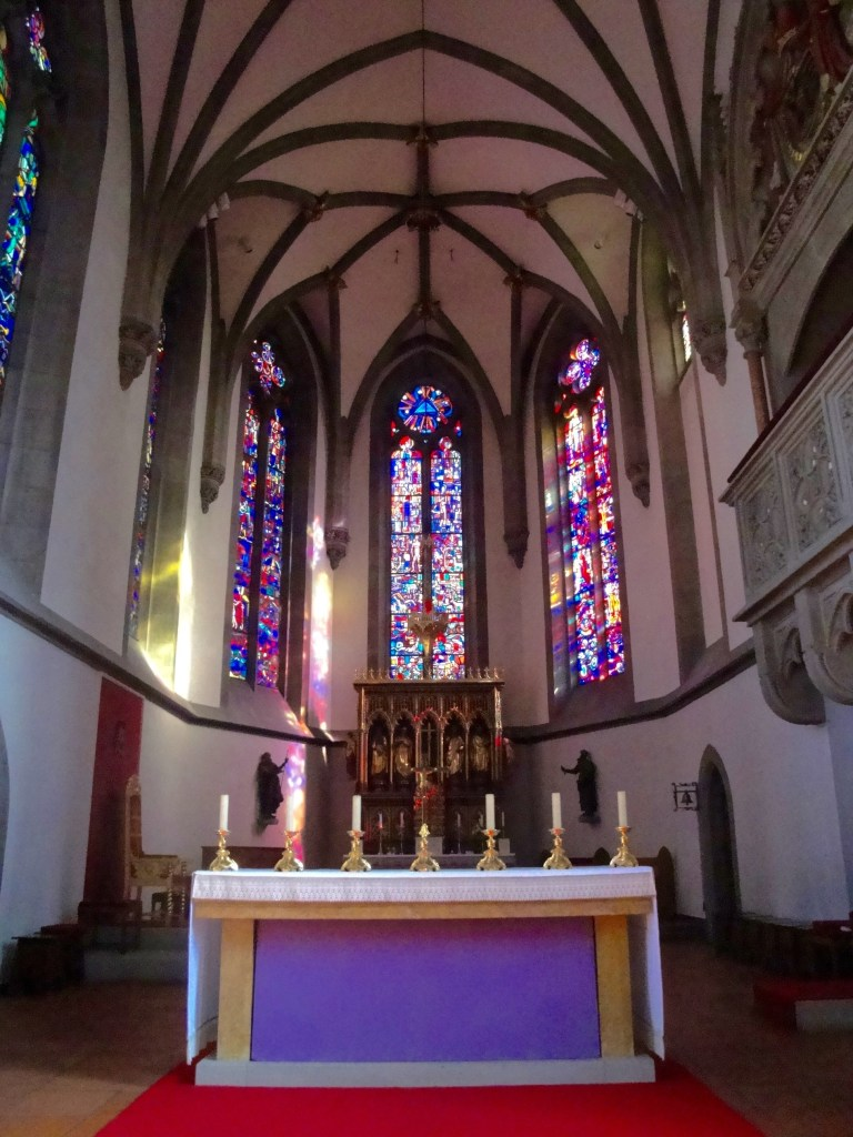 Stained glass in the apse of St. Florin's Cathedral casts colorful shadows on the inside of this baroque-styled church - Vaduz, Liechtenstein