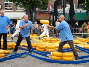 The men throw the wheels of cheese to each other once they pass inspection - Alkmaar, Netherlands