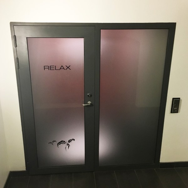 "Door with opaque glass that reads ""RELAX"" - entrance to sauna"