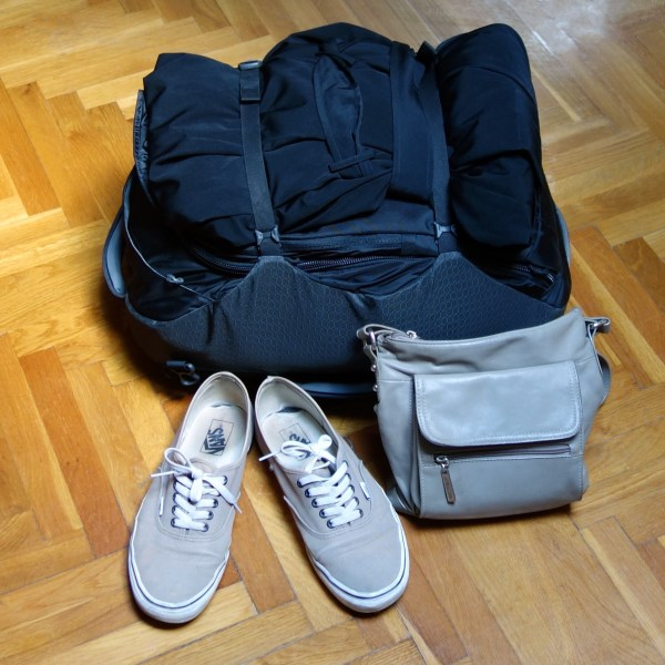 A small packed bag, pair of shoes, and a crossbody purse