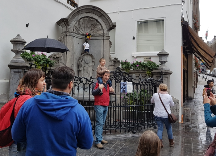 Tourists taking photos of Manneken Pis in Brussels, Belgium