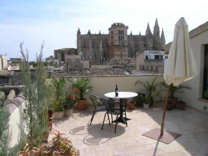 The rooftop terrace at the Dalt Murada, a historic city centre hotel in Palma, Mallorca, Spain, with a view of Palma Cathedral