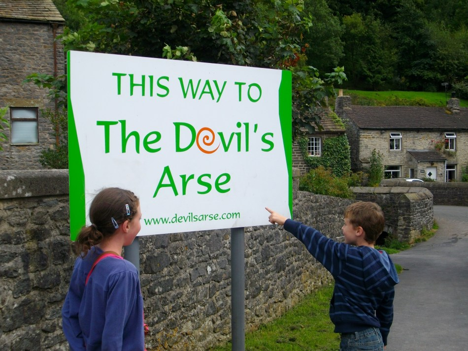 Child pointing at the Devil's Arse sign on a travel adventure