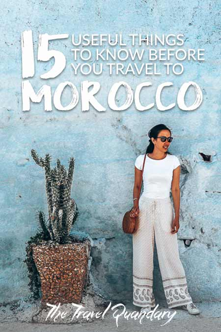Jasmine of The Travel Quandary stands in front of a blue painted wall and next to a cactus plant in Chefchaouen, Morocco