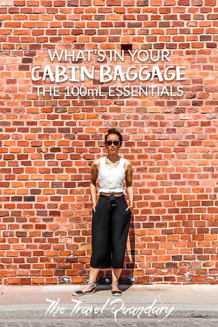Jasmine of The Travel Quandary poses in front of a red brick wall in Krakow, Poland