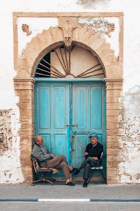Two men sit outside blue door in Essaouira Morocco