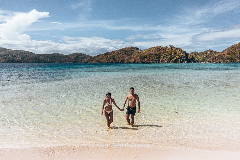A couple wade through the shallow waters on Malcupuya Island, Coron
