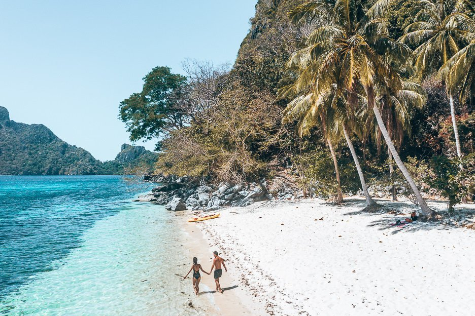 A couple walk along Ipil beach with a kayak in the background, El Nido