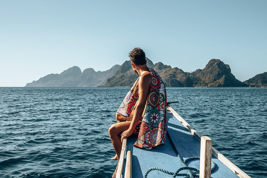 A man sits at the helm of a boat with a towel draped over his shoulders looking out towards the horizon, El Nido