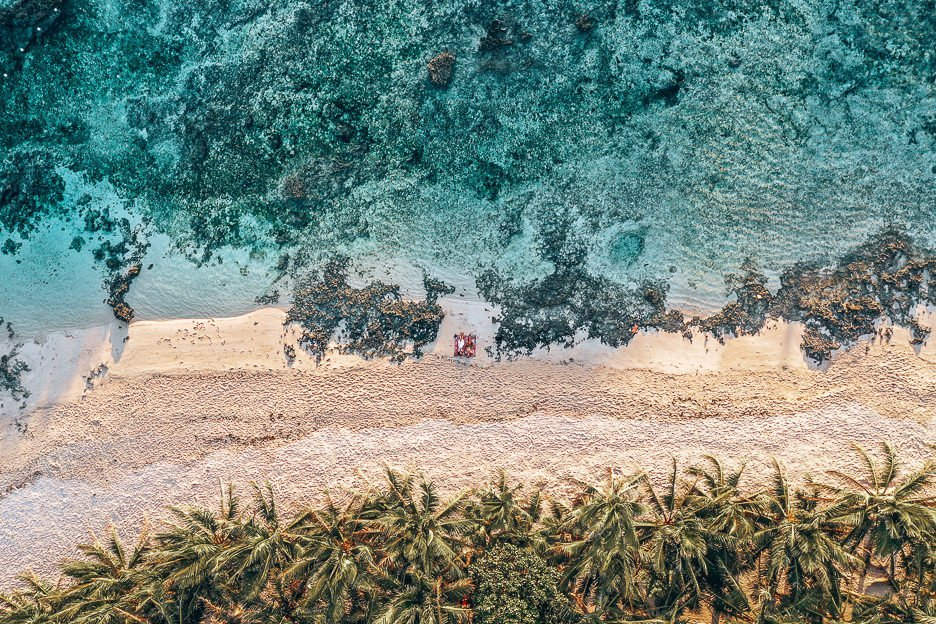 An aerial view of Cloud Nine beach. The ocean, sand and palm trees. A couple lie on a beach towel between the rocks.