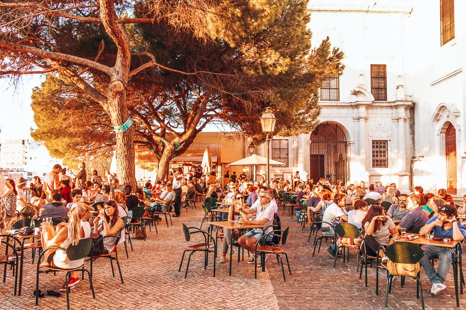 Crowds sit in the afternoon sun at Terrace Bar Esplanada, Lisbon