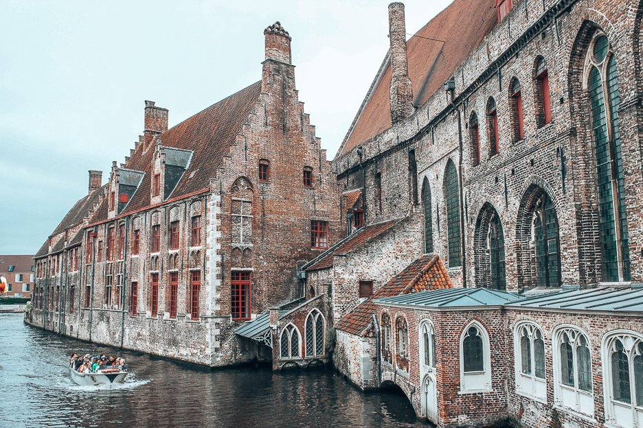 A boat on the canal goes by behind museum Sint-Janshospitaal, Bruges Belgium
