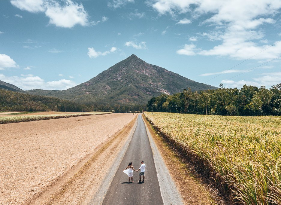 A couple walk along Behana Gorge Road with Walsh's Pyramid in the background, Queensland