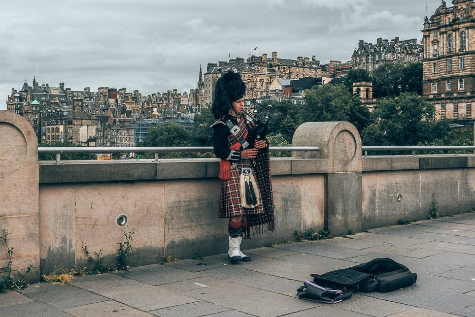 A man in traditional Scottish dress plays the bagpipes, Edinburgh, Scotland