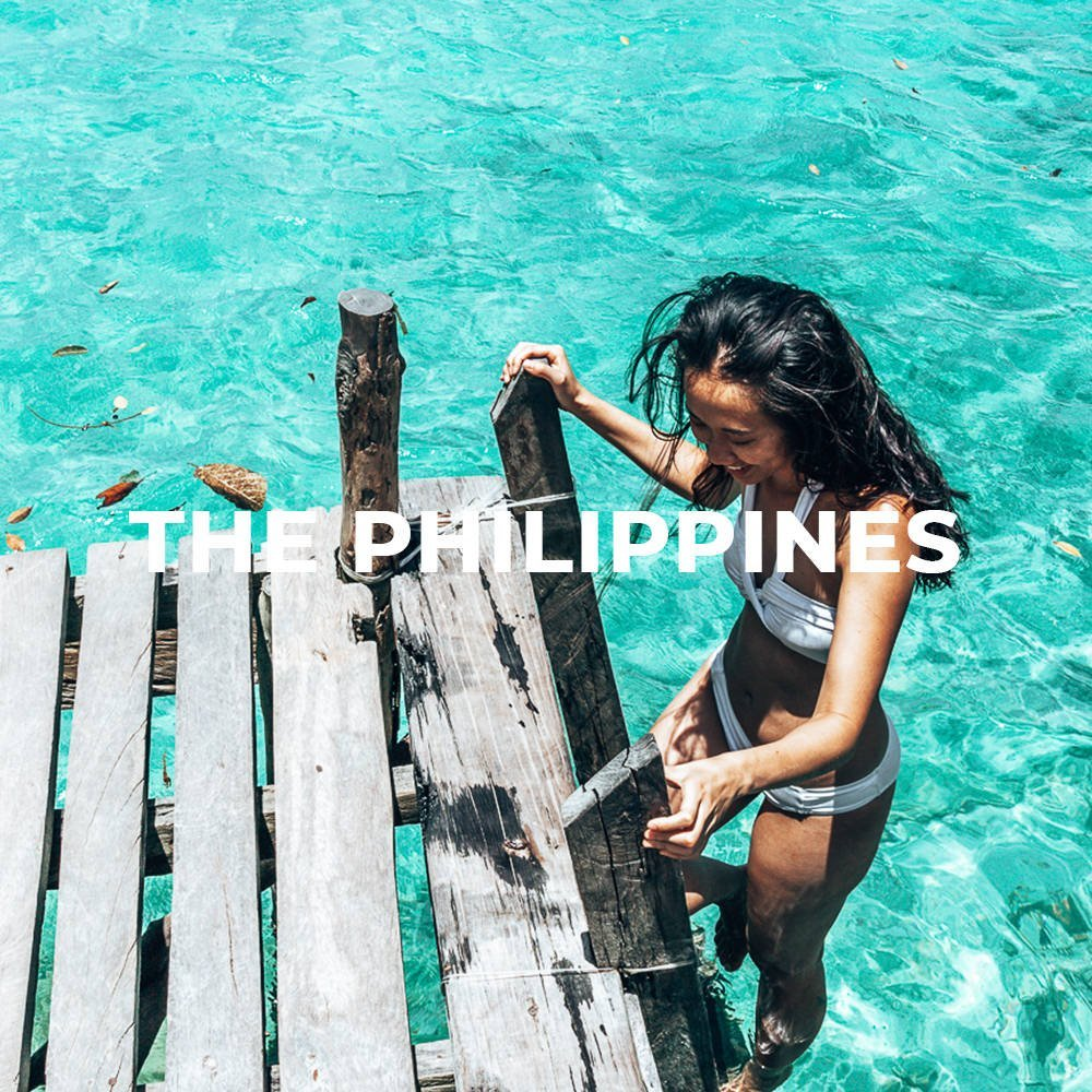 A girl climbs up a ladder from the sparkling blue water in Sugba Lagoon, Siargao, the Philippines, Asia