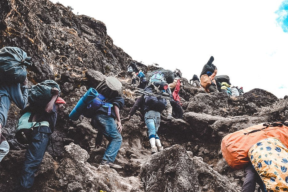 Porters carrying their loads up the Barranco Wall on Mt Kilimanjaro