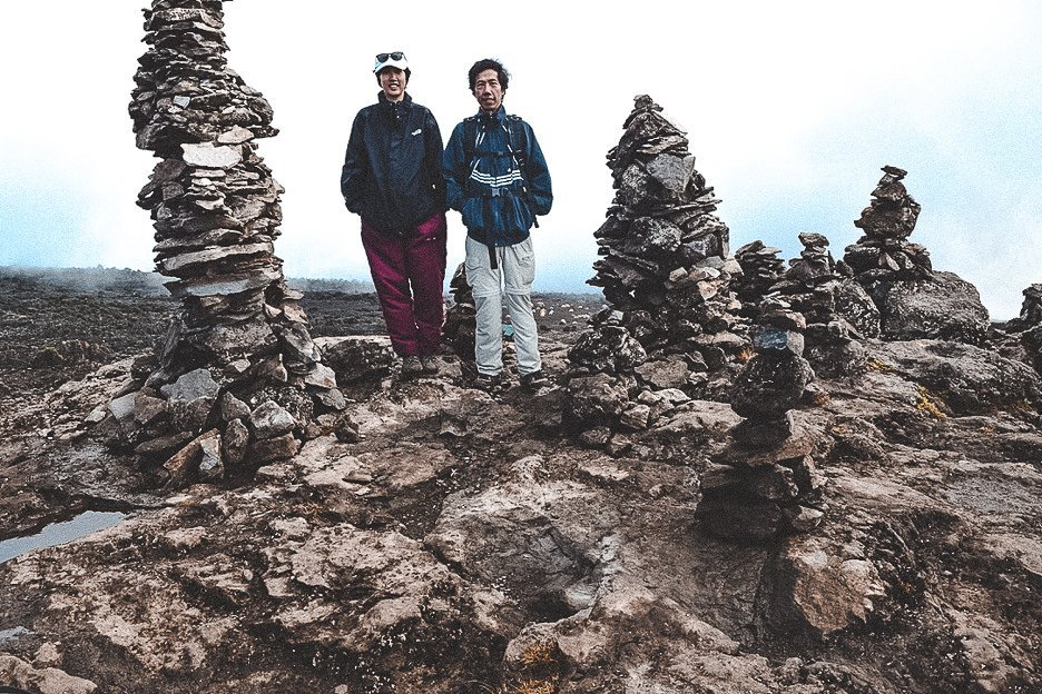 Jasmine and her dad standing among rock formations close to Shira Camp on the Machame Route over 7 days