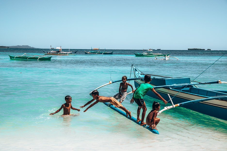 Young children jump off a traditional Filipino boat into the water, Siargao