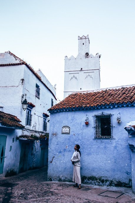 A woman wears a white dress standing in front a blue building in Chefchaouen, Morocco
