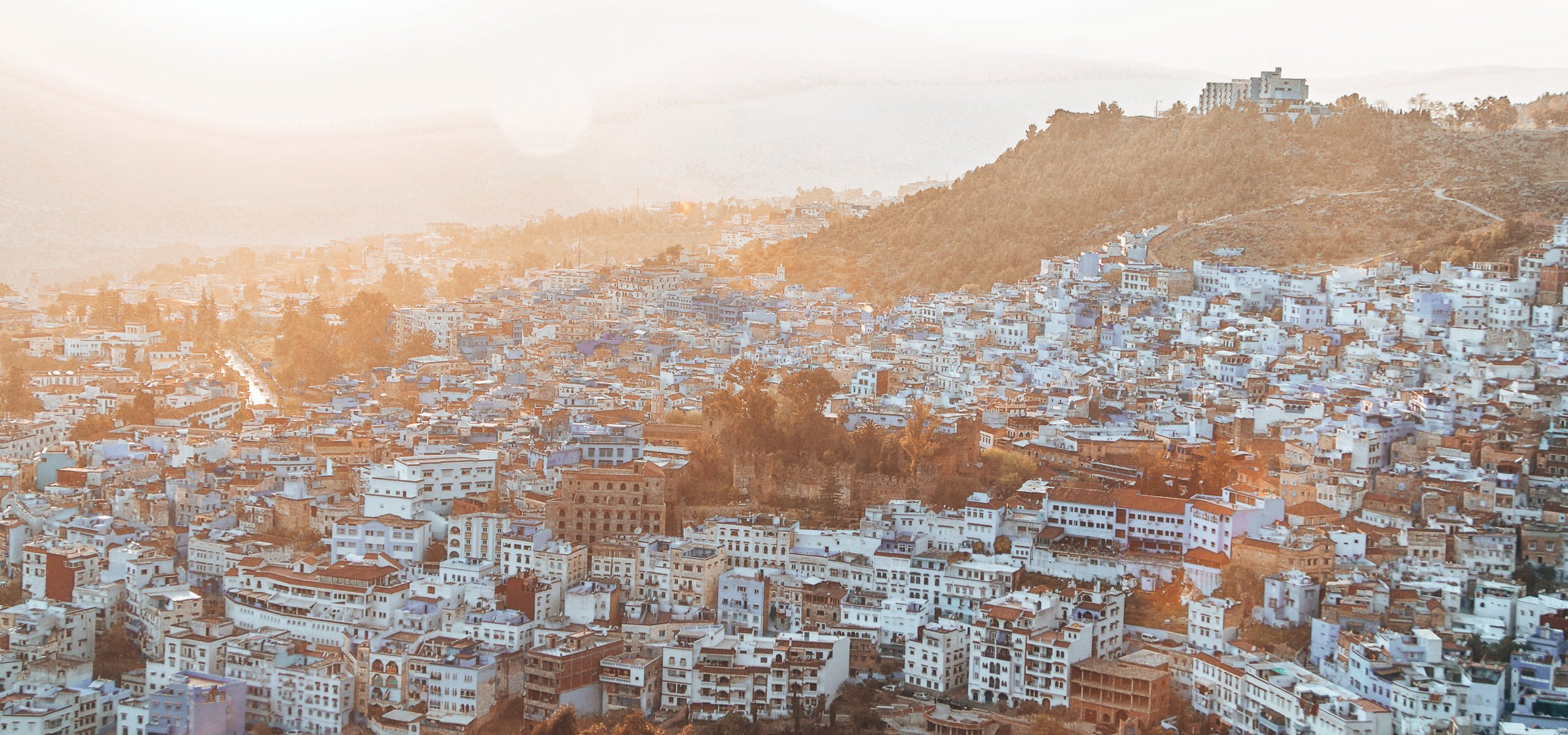 How many days in Chefchaouen | The sun sets over Chefchaouen, lighting up the blue city with a soft golden glow, Chefchaouen