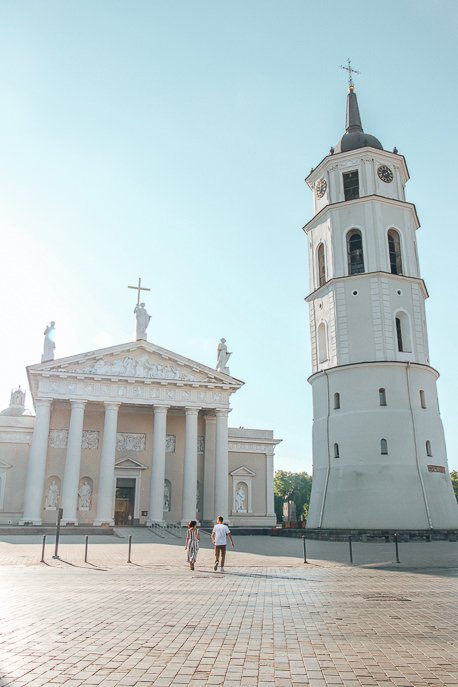 A couple walk in front of Vilnius Cathedral at sunrise, Vilnius - 5 Things When Dating Travelling