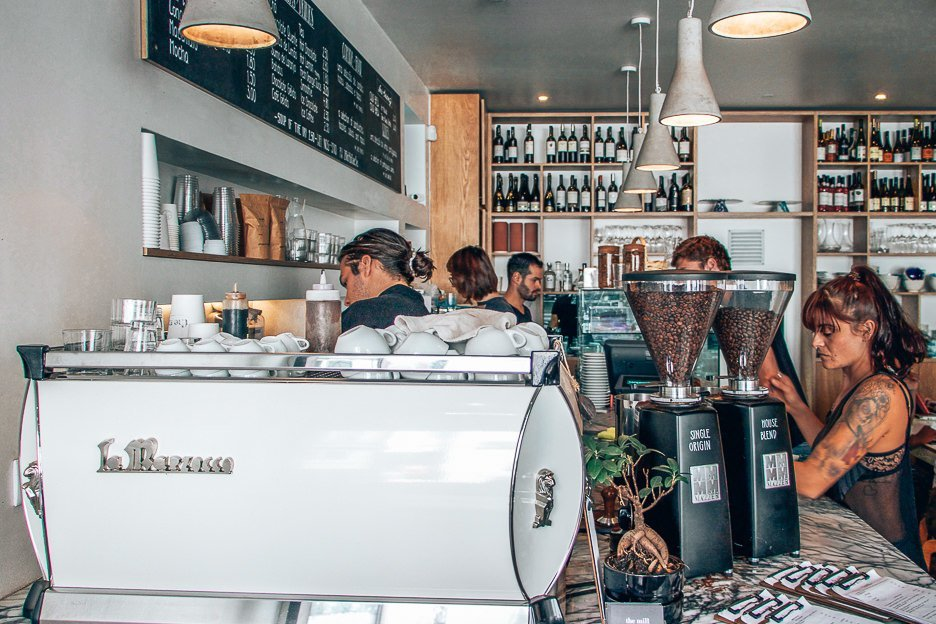 Baristas and wait staff work hard behind the coffee counter at the Mill cafe in Lisbon, Portugal