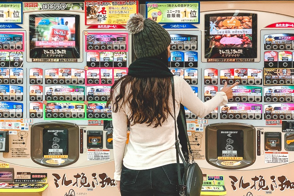 A girl presses a button for coffee from a Japanese vending machine