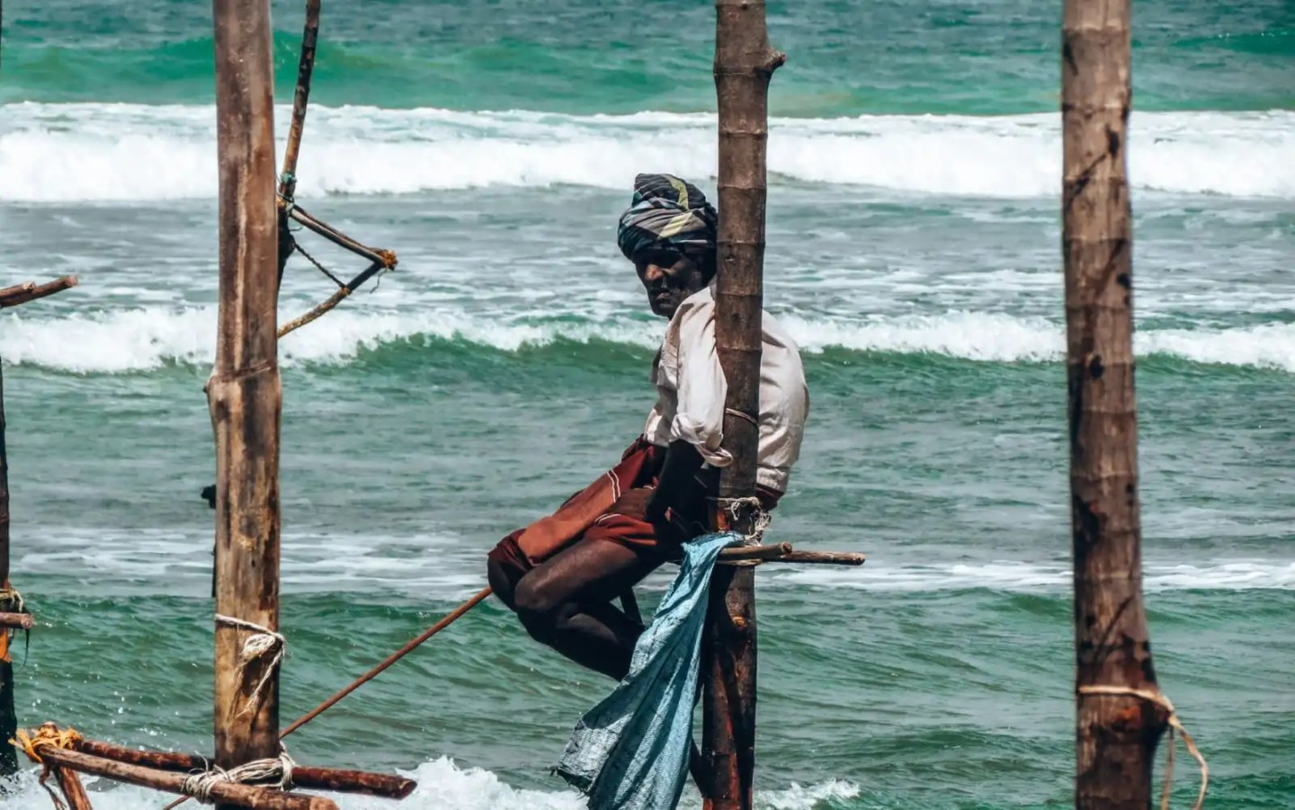 Fisherman perched on small bamboo pole in the Indian Ocean