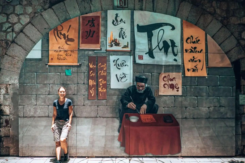 Girl standing in front of mural wall in Hanoi Vietnam