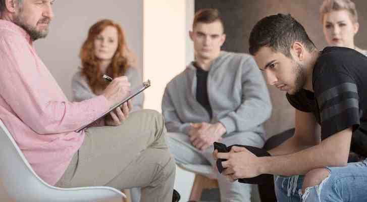 Young man listens while participating in therapy session