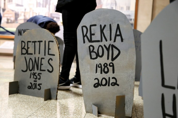 Youth organizers of #NoCopAcademy wrote the names of lives lost to police violence on makeshift headstones during a protest at City Hall