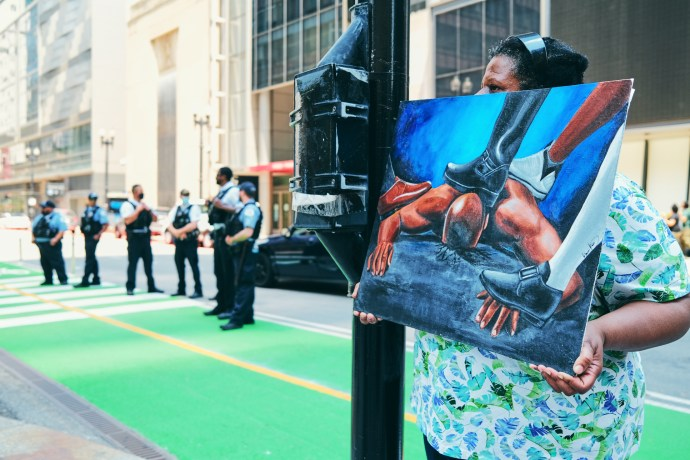 A woman holding a painting of a Black man suffocating with feet on his neck | Photo by Darius Griffin/The TRiiBE