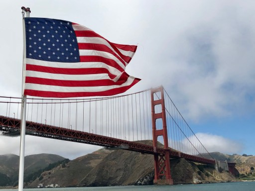 View of the orange vermillion Golden Gate Bridge from the bay, with the American flag blowing in the foreground.