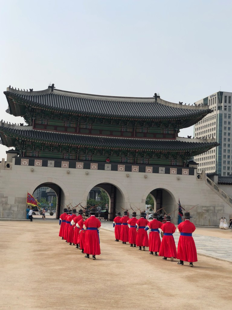 The guards in their brilliant red uniforms march in front of the main gate during the Changing of the Guard Ceremony