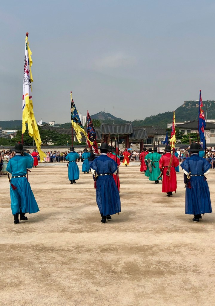 Guards in their colorful uniform carrying bright flags march into the main courtyard.