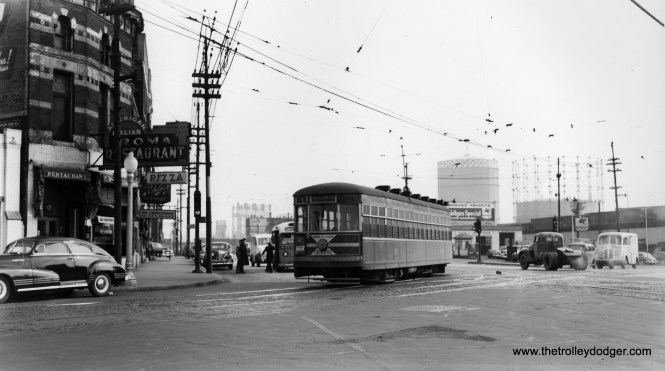 """According to Andre Kristopans, """"The #5 with 3376 is looking SE on South Chicago at Commercial. Note the railroad lift bridges in the distance, past 95th. Also, the bus behind the car is a Chicago & Calumet District bus running on the route that partially replaced the joint CSL/HWEC carlines to Hammond and East Chicago, though the bus route ended up going thru Whiting and then east to Gary, with connections at 119th and Indianapolis for Hammond and East Chicago."""" (Joe L. Diaz Collection)"""