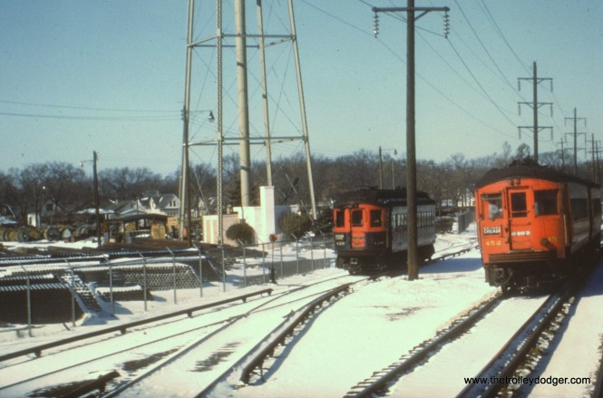 #8 - WS: At left is the Commonwealth Ave yard east of first Ave, Maywood. Train at left is E/B, train at right is W/B. View looks west. EM: CAE 428 (Cincinnati, 1927) and 452 (St. Louis, 1945) with another St. Louis car behind it in winter. AK: Between river and First Av – Northern Illinois Public Service property on left, now site of Maybrook Court.