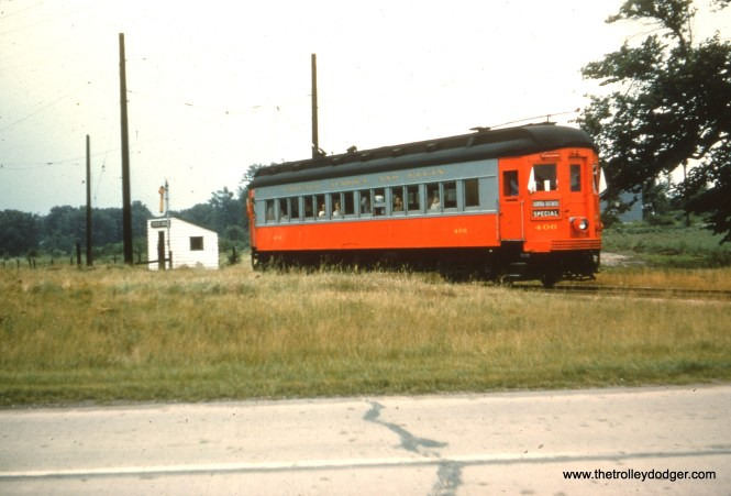 #76 - JN: Westbound at State Rd on Batavia branch under short section of wire to clear the gap in third rail while crossing the road. EM: CAE 406 (Pullman, 1923) again painted red at the State Road flag stop.