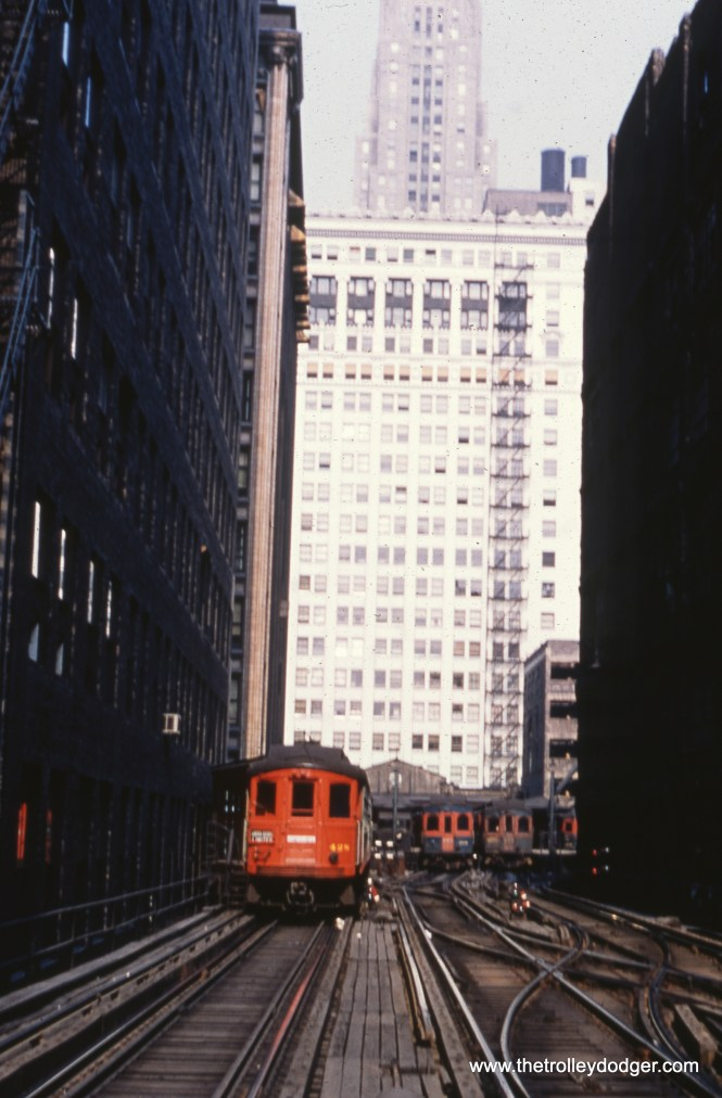 #85 - JN: Wells St. terminal facing east EM: In the caverns between the tall buildings of downtown Chicago looking east at the Wells Street Terminal. At the time this picture was taken, and for quite a few years earlier, this terminal was used only by the CAE. CTA trains turned south after crossing the river to Van Buren street to enter the loop at this time.
