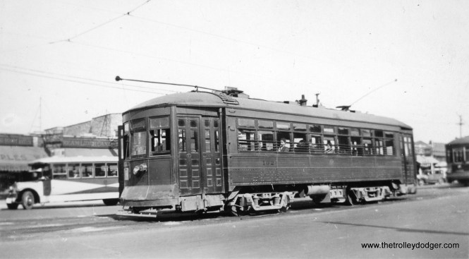 """Chicago & West Towns 102 is shown at Cermak and Kenton in October 1935, with a Chicago Surface Lines route 21 car at rear. Within a few years, C&WT streetcars were repainted into the more familiar blue. Bill Shapotkin adds, """"By the way, what bus is that depicted at left in this photo at Cermak/Kenton? Presume it is a West Towns bus (in the """"sun burst"""" paint job) -- but if so, what route is it working? If not a West Towns' bus, then whose might it be and what route is it working?"""""""