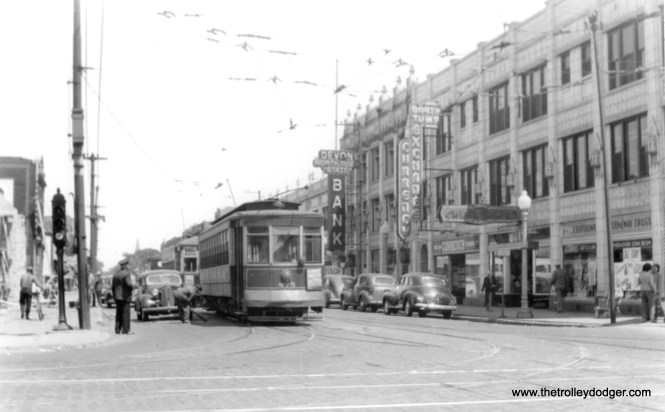"""George Trapp writes, """"875 on Devon followed by 169 class, both cars are pull outs from Devon barn for Western shortly before Western route shortened in Aug. 1948. 169 class cars used as two man on Western, Halsted and Ashland after being displaced by PCC's on Broadway-State until CTA one manned them."""" This is the corner of Devon and Western, because the Devon-North Town State Bank was then located at 2345 W. Devon. We are looking east. (Edward Frank, Jr. Photo)"""