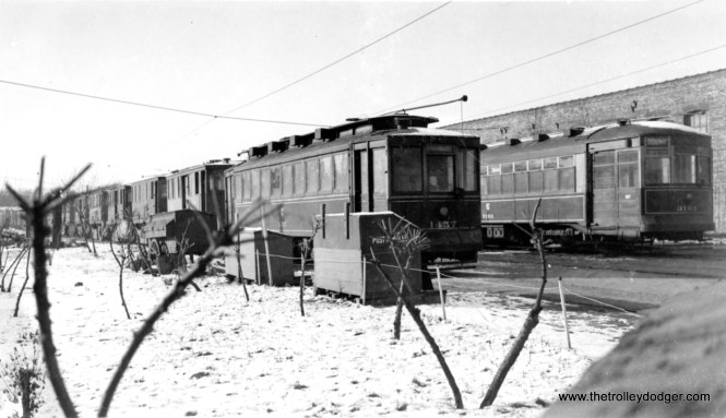 """CSL 1457 and 3193. The former car appears to be in work service. According to Don's Rail Photos, it was """"rebuilt as salt car AA68 in 1948."""" George Trapp writes: """"CSL #1457 and 3193 are in the South open yard of the Devon Depot, open area to left later used for additional storage tracks added in mid 1940's for PCC's which included an additional single track repair bay added to the south side of the existing building and a stand alone single track brick building along the south property line which housed an automatic car washer."""" Another reader: """"Devon Station (Clark and Schreiber)."""" Andre Kristopans: """"1457 was a salt car in the 30″s. When the 36 PCC's came, many 13-1400's were made into salters. Some went back to passenger service during WW2, rest were r# AA's either by CSL after the war or CTA in 1948. """""""