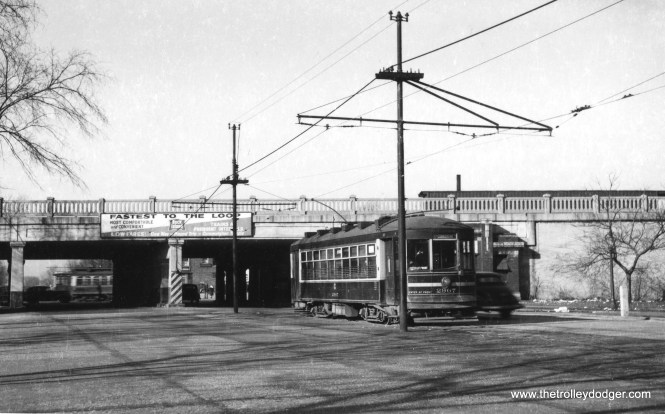 "CSL 2907, at the west end of the 87th Street route. Jon Habermaas writes: ""The line ended east of the Rock Island viaduct, and there was no connection to the tracks on Vincennes. The car has changed ends and is ready for a new trip eastbound on 87th."" (Railway Negative Exchange Photo) M. E. adds, ""The 87th St. streetcar line's west end was on the east side of the Rock Island main line. Therefore, the streetcar shown has ended its run on the westbound track, switched trolleys, and is ready to head back east. On the west side of the railroad viaduct is Vincennes Ave., on which is a Halsted-Vincennes car. Just to the east of this view on 87th St. is Halsted St."""