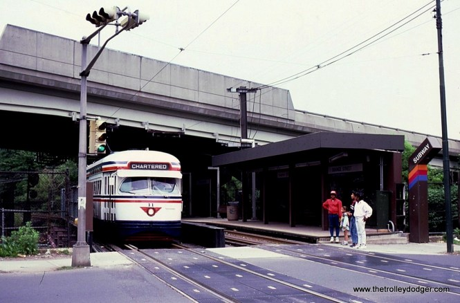 PCC 11, still in the Transport of New Jersey Bicentennial colors, is stopped at the soon to be replaced Orange Street Station. Here the subway crosses over the ex-DL&W Morris & Essex Line and the bridge is in need of replacement. To accommodate this work the station was moved across Orange Street to it's present site.