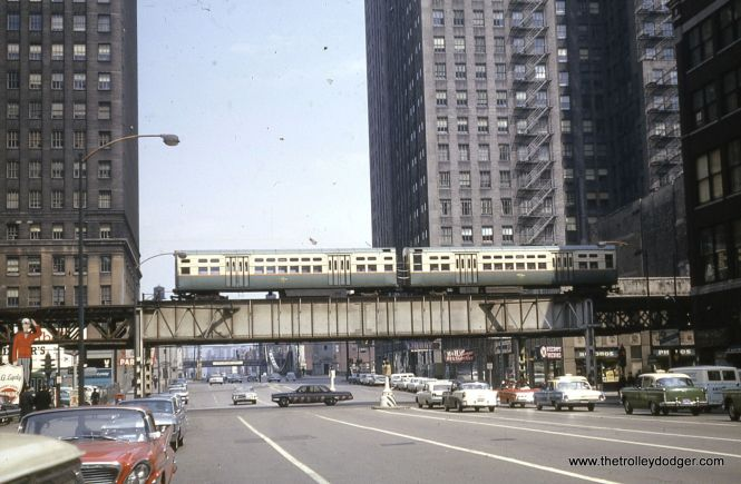 """A two-car train of CTA 6000s heads west at Lake and LaSalle in April 1964. Below the """"L"""" at right, we see the Loop location of Discount Records, a local chain who once had a great selection of LPs."""